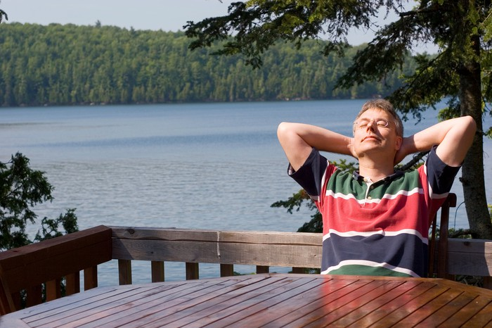 A man relaxes on a porch overlooking a lake.
