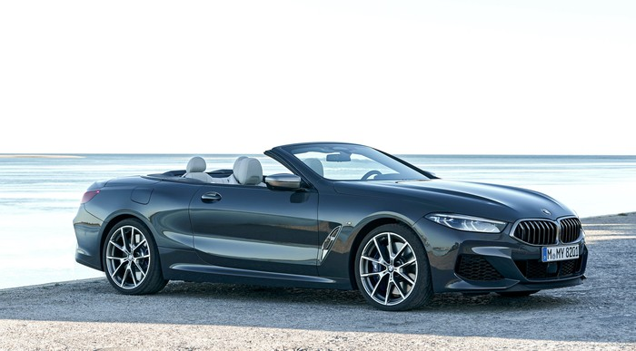 A gray BMW 8 Series convertible, parked on a beach.