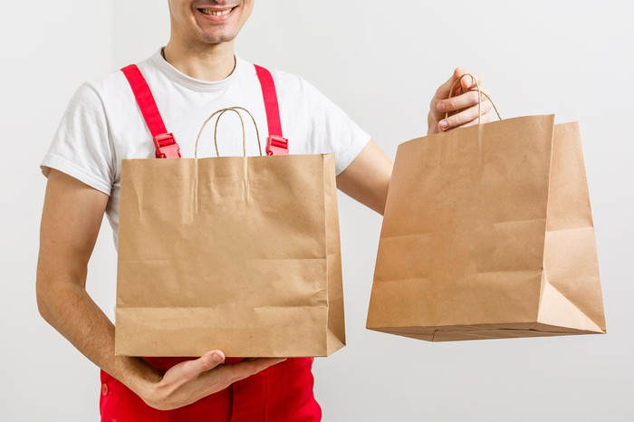 Restaurant delivery boy with two bags of food