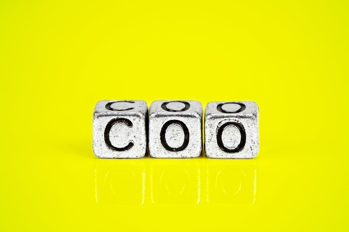 Three blocks that spell out COO on a yellow background