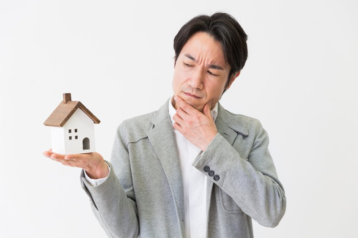 A person looking at a miniature house while holding his chin in a pensive manner.