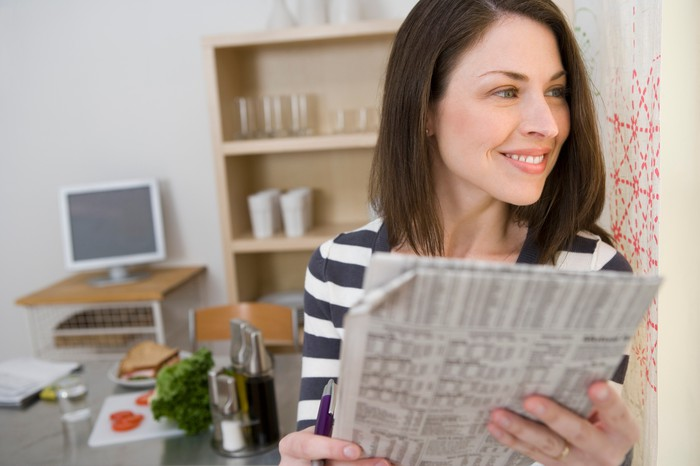 A smiling woman holding a financial newspaper with stock quotes while looking off into the distance.