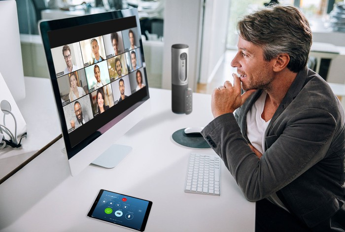 Middle-aged man sitting at a desk in front of a computer screen showing 12 images of people on a videoconference call.