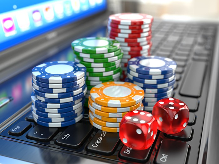 Casino chips and dice sitting on computer keyboard