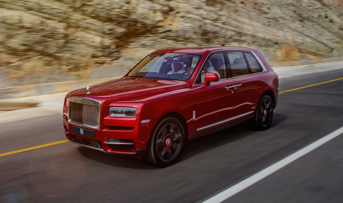 A red Rolls-Royce Cullinan, an ultra-luxury SUV, on a mountain road.