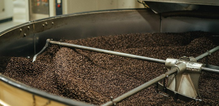 A large roaster full of coffee beans.