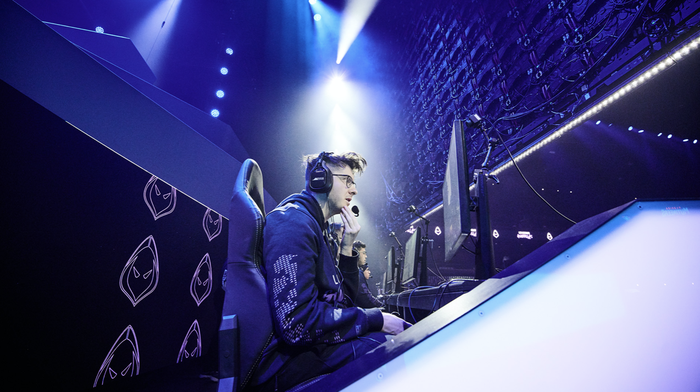 An esports player sitting in front a PC and wearing a headset during a competitive match.