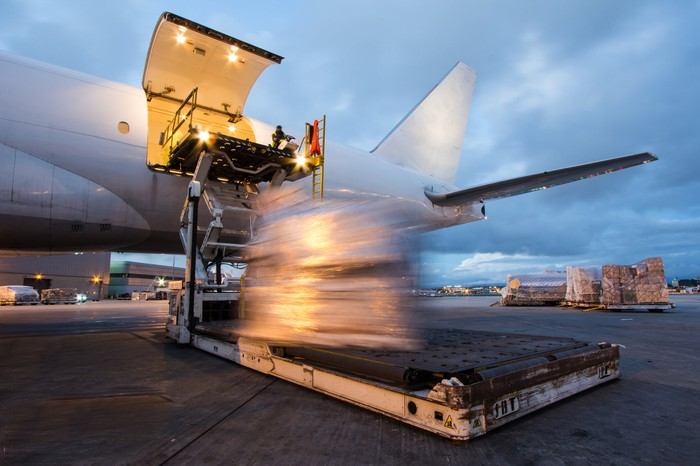 Cargo is unloaded from the back of an airplane.