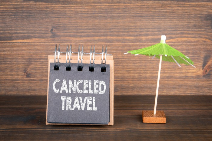 Chalked sign reads Canceled Travel next to a small drinks umbrella