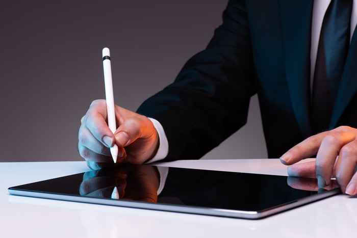 A businessman sits with a stylus in hand, ready to sign a tablet computer on the table in front of him.