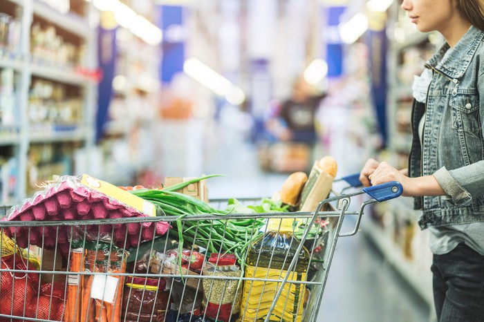 Woman pushing shopping cart full of food