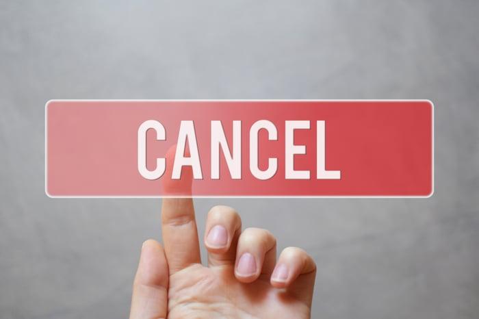 "A hand pressing a semi-transparent ""cancel"" button"