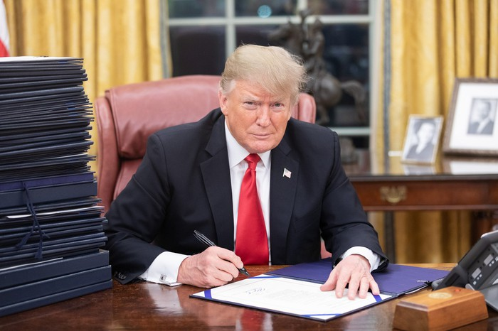 President Trump signing paperwork at the Oval Office desk.