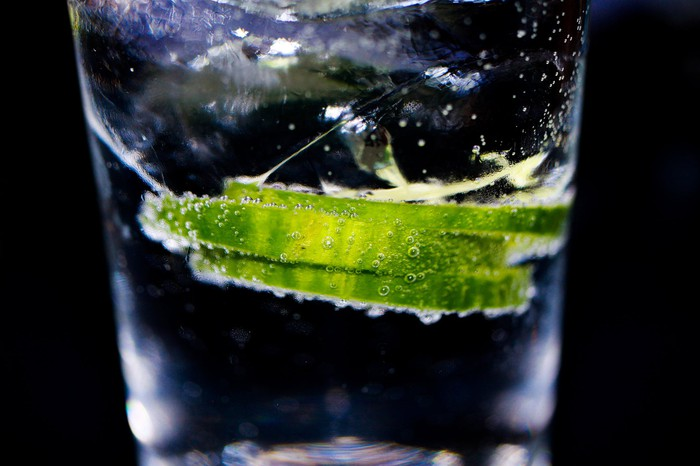 A close-up photo of a gin and tonic drink is shown against a black background.