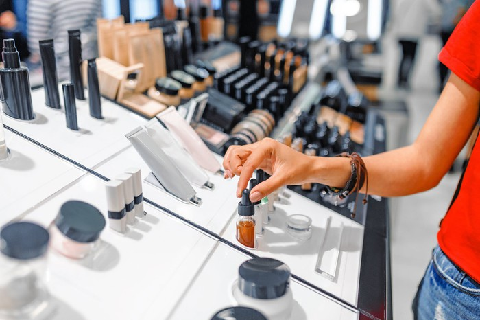 A hand reaches for a skin solution dropper in an aisle in a makeup store.