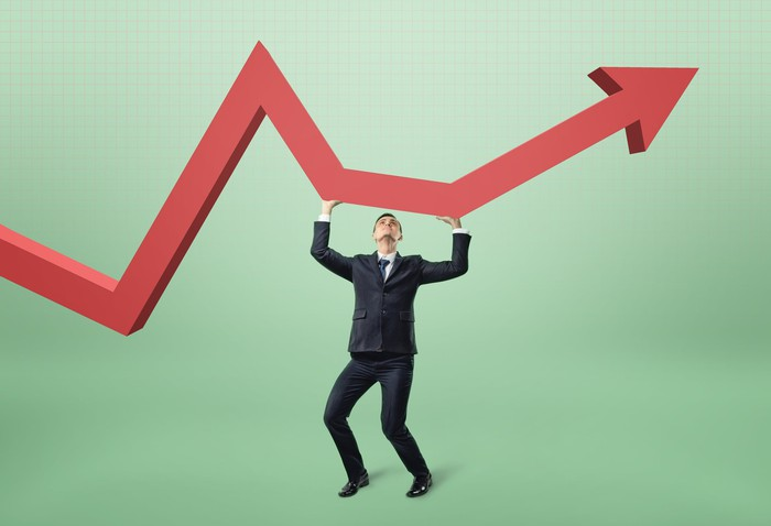 A man in suit supporting a huge red stock chart arrow