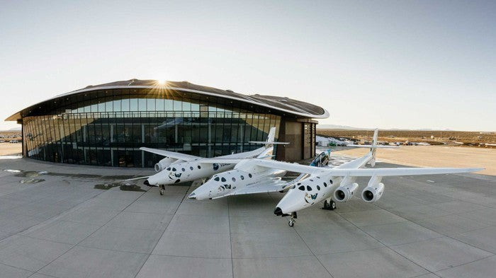 Three spacecraft parked in front of Spaceport of America building with blue sky in background.