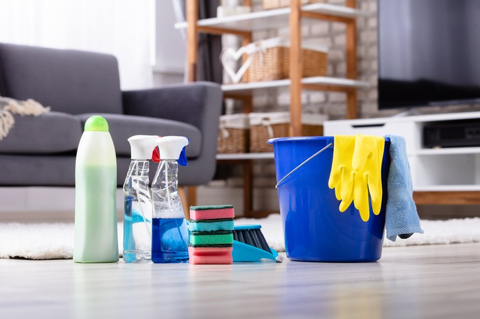 Cleaning supplies, a bucket, and rubber gloves on the floor of a living room