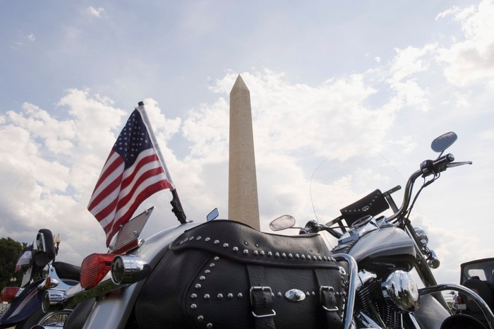 A motorcycle with an American flag parked in front of the Washington Monument