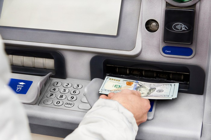 Person at ATM holding hundred-dollar bills