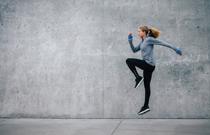 A young woman in athletic apparel works on cardio training beside a cement wall.