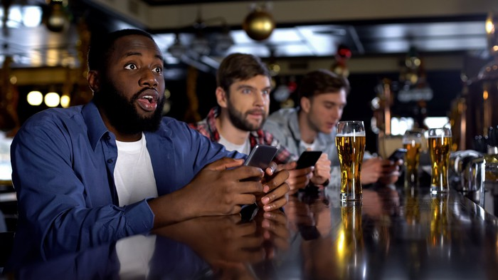 In a bar, men watching sports wager using online apps