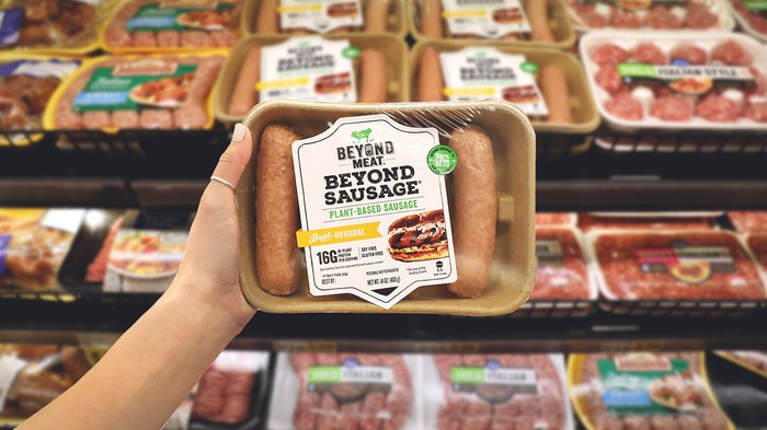 A hand holding up a package of Beyond Sausage.