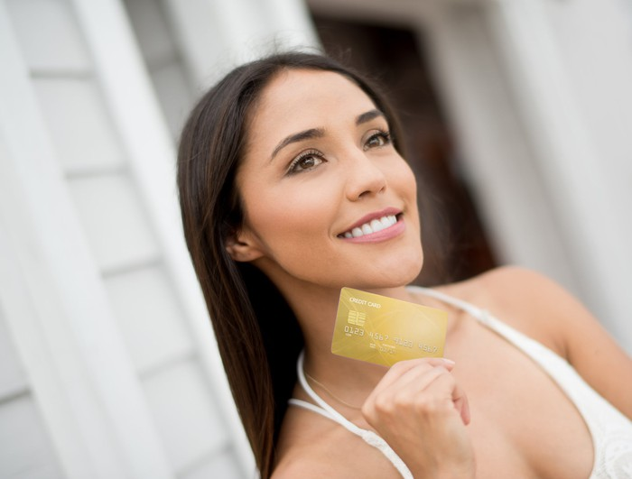 A smiling woman holing up a credit card in her right hand.