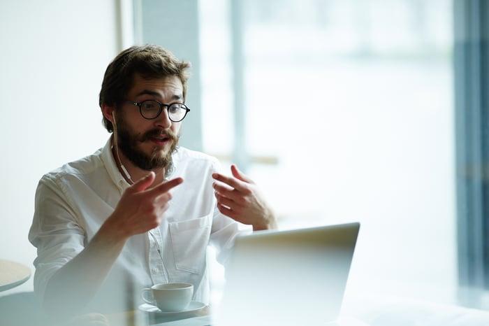 Man at laptop gesturing at laptop screen