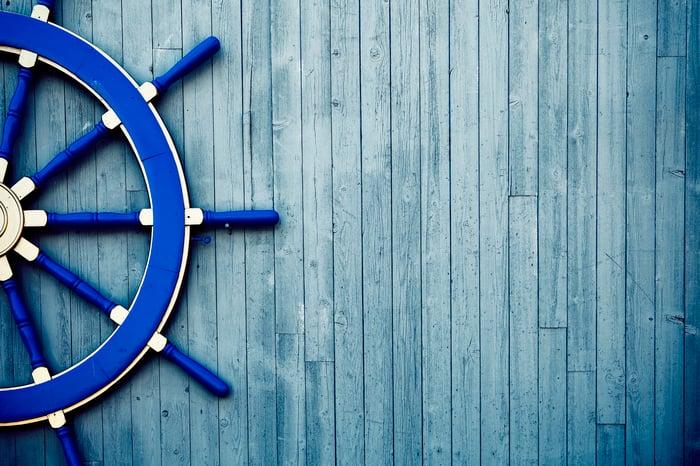 A blue vintage yacht helm wheel lies on a wooden deck.