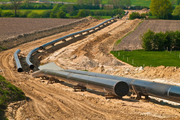 A pipeline under construction winding its way through country fields