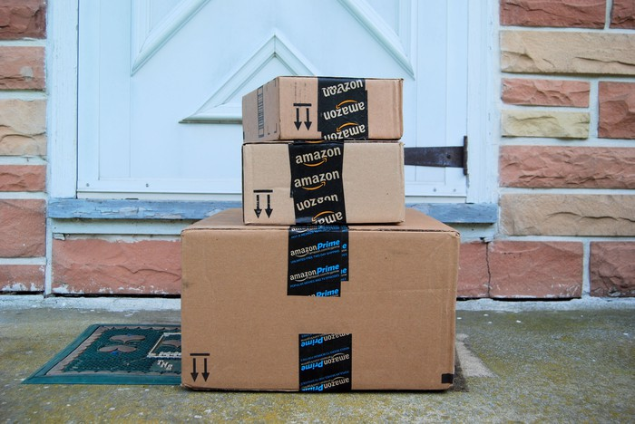 A stack of Amazon boxes outside a door.