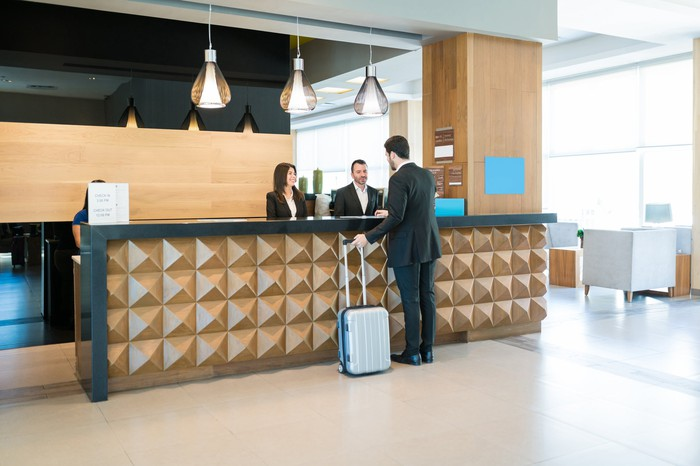 A man with a suitcase checks in at the front desk of a hotel.