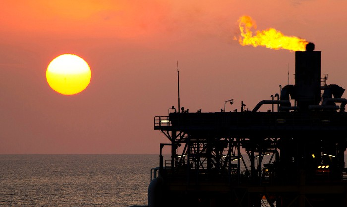 Gas flaring off an offshore oil platform with the sun in the background