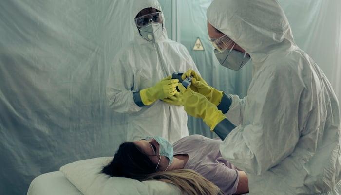 Doctors in Hazmat suits treat sick patient