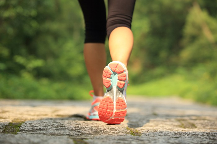 Close-up of a woman's shoe as she runs on a trail.