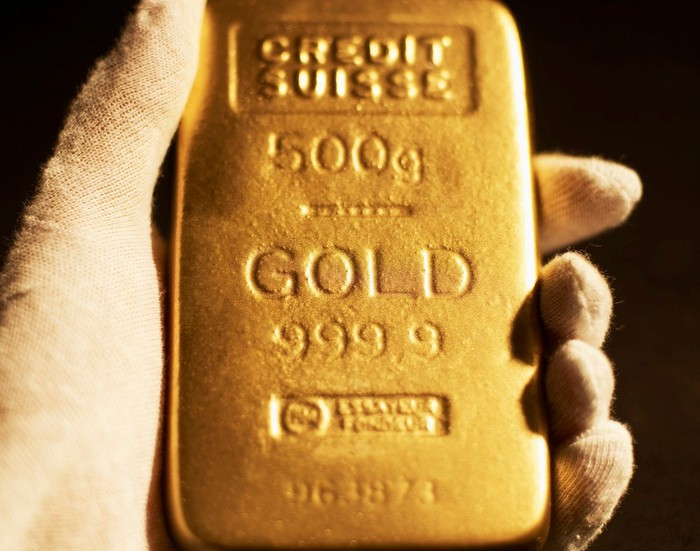 Hand holding a small gold brick.