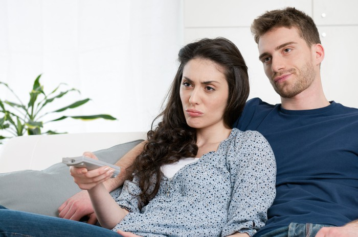 Bored young couple holding a remote and watching TV