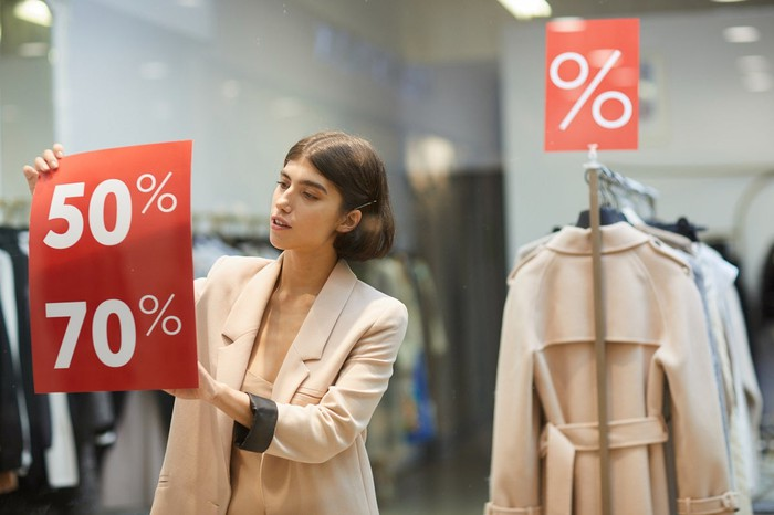 Woman putting Discount signs in a shop window