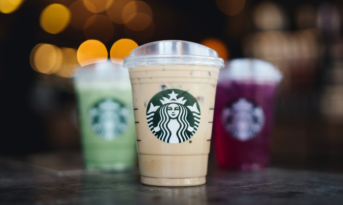 Three Starbucks cold-drink cups with logos visible.