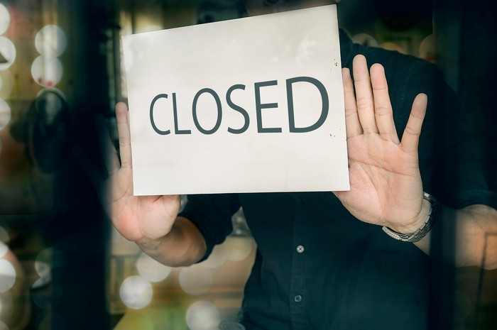 A person posting a sign with the word closed on it.