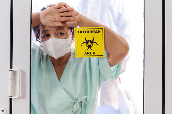 "Patient wearing a mask with her hands against a glass door with a sign stating ""outbreak area"""