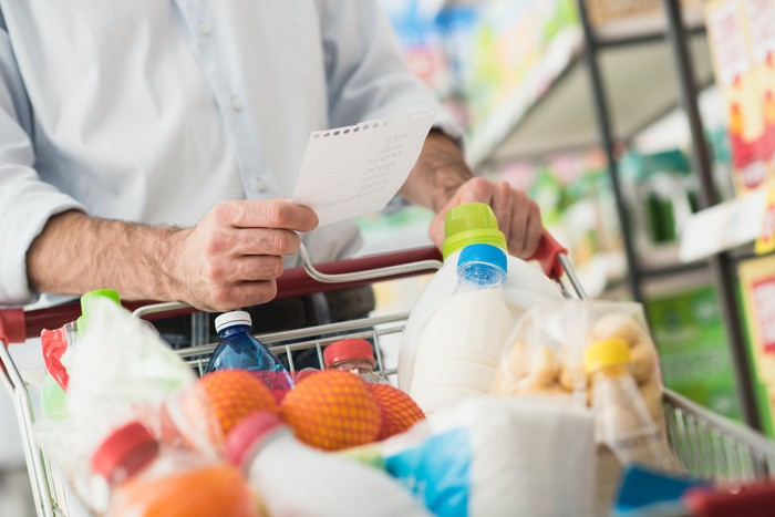 Man holding piece of paper and pushing shopping cart full of grocery items