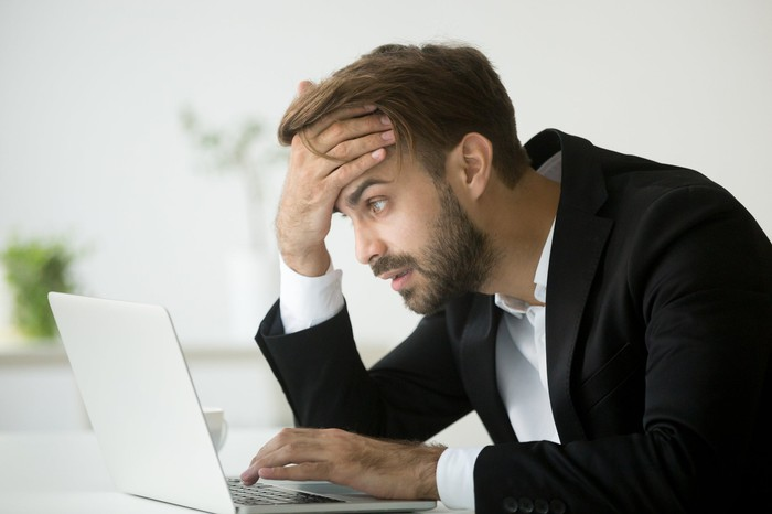 A young man in business casual clothes is distraught in front of his laptop.