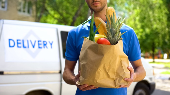 A delivery person delivering a brown bag of groceries.