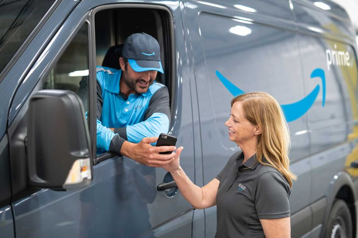 An Amazon delivery van driver showing his phone to a woman standing outside the van.