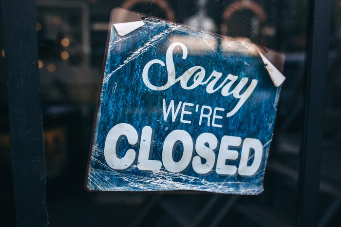 Sorry We're Closed sign hung in window