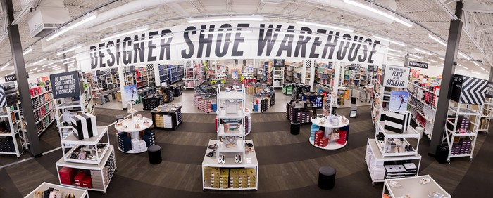 In a store, a banner displays Designer Shoe Warehouse.