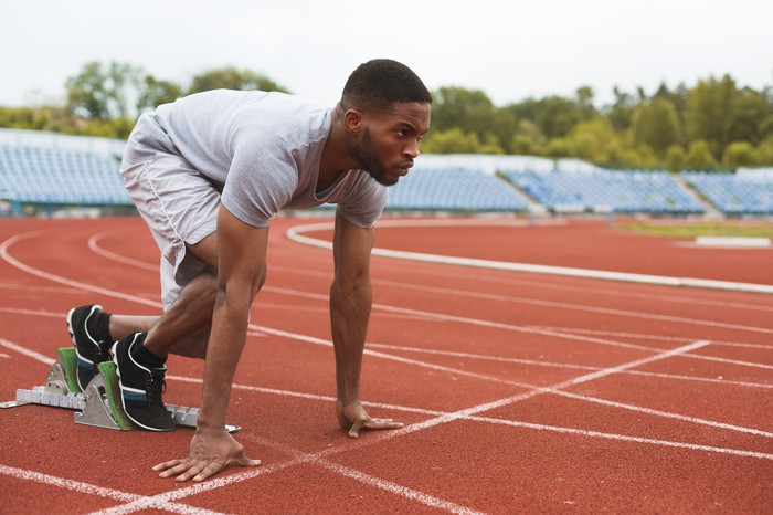 A man on a starting block on an outdoor track