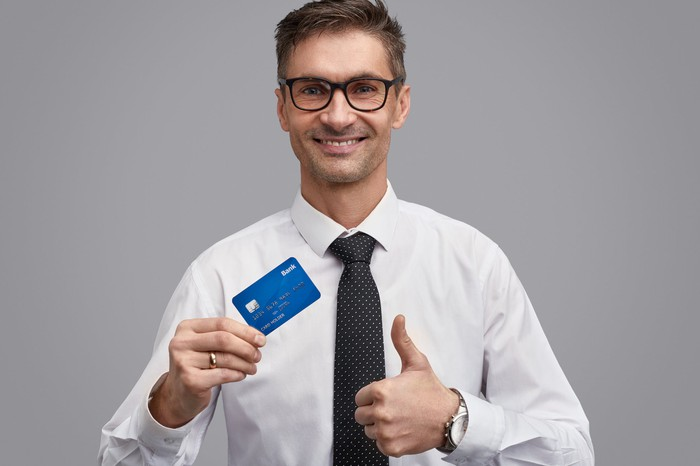 Businessman giving thumbs up while holding a credit card